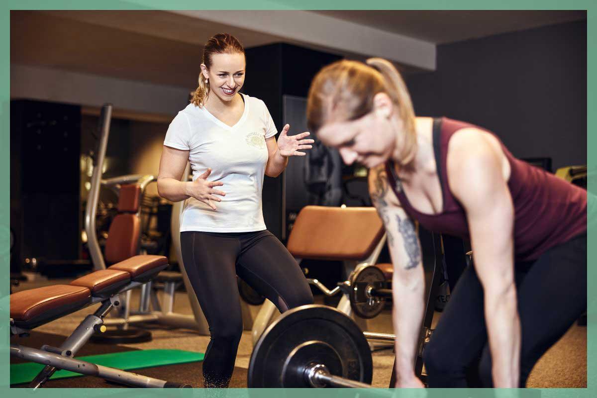Personaltrainerin und Frau trainieren im Fitnesstudio Oberkörper und Arme.